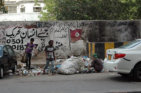 against all odds: PAKISTAN_KARACHI_3 males collectin recycling goods from waste this is dailylife for some collecting waste and make living while on back ground onw all black paint slogan reads Against all odds cruelity and crime ,man kind live along  movement 13 May 2012