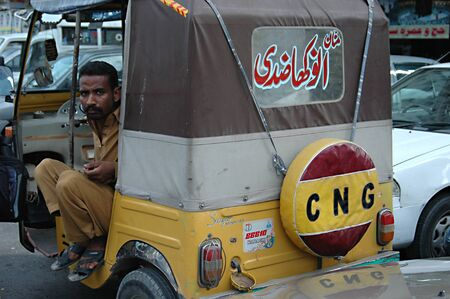 PAKISTAN_KARACHI_Motor rickshaw male waiting for client for ride 17 May 2012