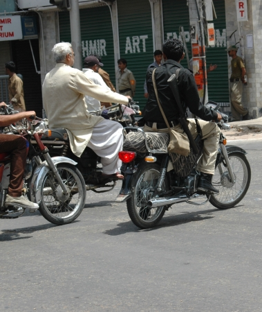 PAKISTAN_KARACHI_ Some Pakistani motor biker do not respect low wearing Helmets while driving motor bike though Karachi Police has warning banner on each road and street corners  18 May 2012 Stock Photo - 14146583