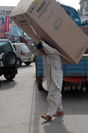 KARACHIPAKISTAN_Pakistani male carry heavy Haier refrigeratro on his back and doing manual dangerous work ,hard to make liging in Indo-Pakistan 13 Sept. 2012