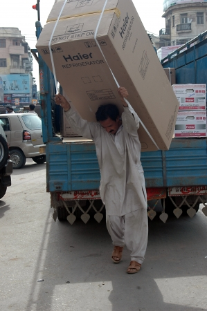 KARACHIPAKISTAN_Pakistani male carry heavy Haier refrigeratro on his back and doing manual dangerous work ,hard to make liging in Indo-Pakistan 13 Sept. 2012         Editorial