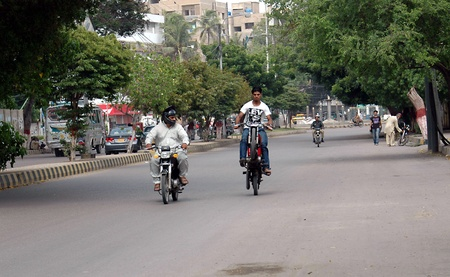 KARACHIPAKISTAN_  Young Pakstan male ride on one wheel on motor bike due to one wheel is demage and he is riding on busy road on one wheel 15 Sept. 2012         Editorial