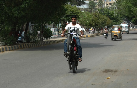 KARACHI/PAKISTAN_  Young Pakstan male ride on one wheel on motor bike due to one wheel is demage and he is riding on busy road on one wheel 15 Sept. 2012        Stock Photo - 15240429