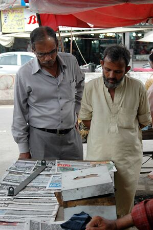KARACHIPAKISTAN_ Pakistani reading dailies news papers at Pakistani news stand to keep uptodate with world view 13 Sept. 2012
