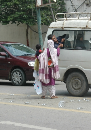 KARACHIPAKISTAN_Small busines vandor Pakistan woman selling cloths pieces to among trafic  and same time she is begging she has tow profession ,business and begging business  13 Sept. 2012