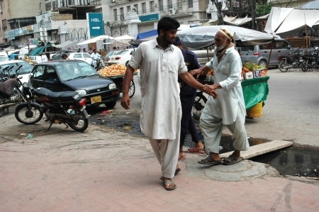 eldlery: KARACHIPAKISTAN_   Pakistani mature males helping a eldlery blind man by passing dirty water 16 Sept. 2012