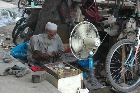 eldlery: KARACHIPAKISTAN_  Senior pakistani shoe maker reparing old shoe and using fan during hot weather in Pakistan and make living there is no social or eldlery retirement fund for eldlery people of Pakistan 16 Sept. 2012        Editorial
