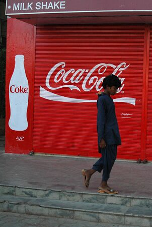 KARACHIPAKISTAN_   Pakistani males pass by closed shop coke or coca cola commercial at shop door today on 4th October 2012