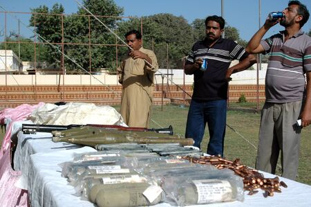 raid: KARACHIPAKISTAN_  Pakistan CID police inspect Seized weapons in raid  and arrested 7 poeple with connection with weapons and bullet, CID police display during press conferece at CID office in Karachi today on 5 Oct.2012