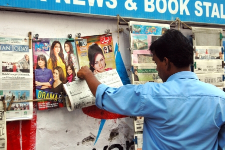 news stand: KARACHIPAKISTAN_   Pakistani male reading sad story of Pakistani young girl Malala Yousafzai in Pakistani news media and dailies at news stand today on 11 October 2012