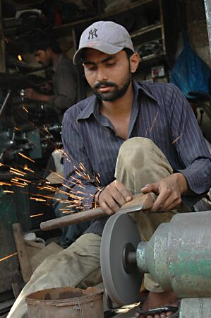 shop keeper: KARACHIPAKISTAN_ Pakistani shop keeper  sharping knives preparing for Holy qarbani slaughtering lambs and other animals during holy  eid season 17 Oct. 2012           Editorial