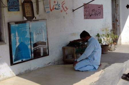 come in: KARACHIPAKISTAN_ Muslim prayer place  male saying his prayer messages read in Urdulanguage this place is for prayer please come and say your prayer here 21 Oct.2012