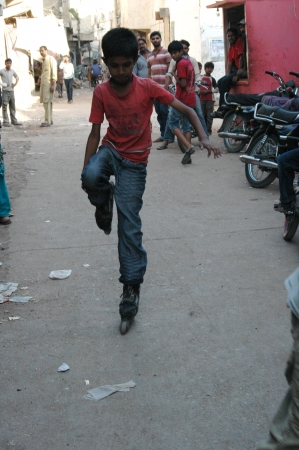 ediroial: KARACHI  PAKISTAN  Pakistani child skates in street in Karachi slums Azam Basti 23 Nov. 2012
