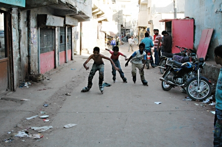 slums: KARACHI  PAKISTAN  Pakistani child skates in street in Karachi slums Azam Basti 23 Nov. 2012