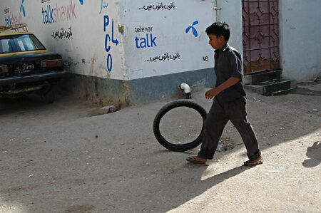 karachi: KARACHIPAKISTAN_Christian boy rolling motor bike  in street lake of play ground in azam basti Karachi slums 24 Nov. 2012