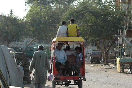 KARACHI/PAKISTAN_  Pakistani is shor´tage of state transport public system  passenger sitting on roof at motor rickshaw 26 Nov. 2012         Stock Photo - 16532521