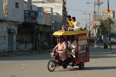 KARACHI/PAKISTAN_  Pakistani is shor´tage of state transport public system  passenger sitting on roof at motor rickshaw 26 Nov. 2012      Stock Photo - 16532517