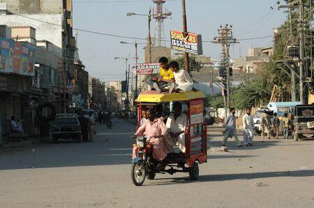 KARACHI/PAKISTAN_  Pakistani is shor´tage of state transport public system  passenger sitting on roof at motor rickshaw 26 Nov. 2012       Stock Photo - 16532524