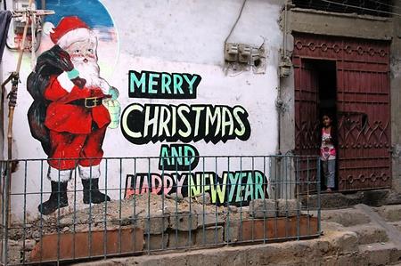 ediroial: Copenhagen  Denmark.  Santa with message Merry Christmas and happy new year on christmas hgome in Azam Basti while christmas girl poses for photographer 26 Nov. 2012         Editorial