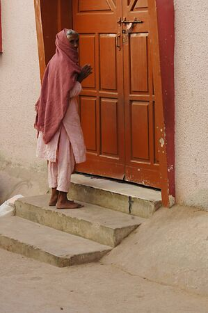 eldlery: KARACHIPAKISTAN_ Eldlere christian woman saying her prayer at Saint Paul Church door steps at Azam Basti 14 Dec. 2012