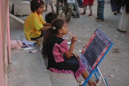 PAKISTAN_KARACH_Christian young girls studing english language in street infront their home in Azam Basti, .oct,28,2013