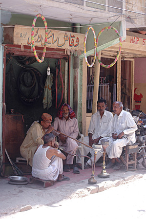 Karachi Pakistan-  Pakistan male smoking water pipe in Pakistani m urdu langaueg called Hoka        01 July 2014