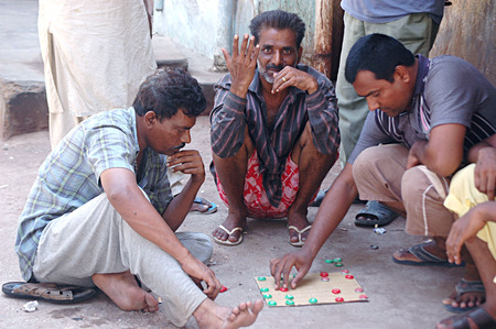 Karachi Pakistan- Mature men using their free time for playing game in Am az Basti street it is usual the men most of time spend outisdee the home instead inside their homes         01 July 2014