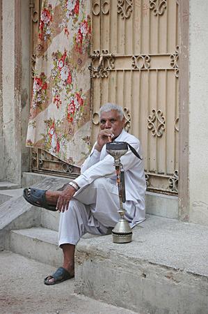 Karachi Pakistan-  Pakistan male smoking water pipe in Pakistani m urdu langaueg called Hoka        02 July 2014   Editorial