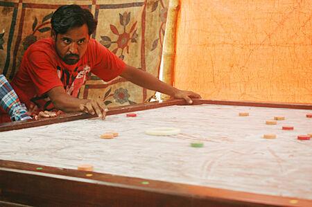 Karachi Pakistan-Male playing kiramboard games today on          03 July 2014 Editorial