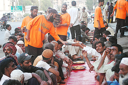 Karachi Pakistan- Pakistani life during ramadan people eating free food at one of local chairty place          07 July 2014