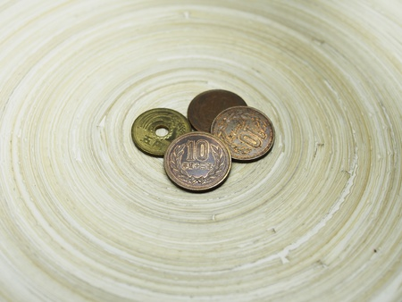focal point: Japanese Ten Yen Coin and Other Coins on Bamboo Circular Tray Stock Photo