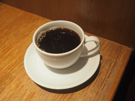 Black coffee in a white cup placed on a wooden table
