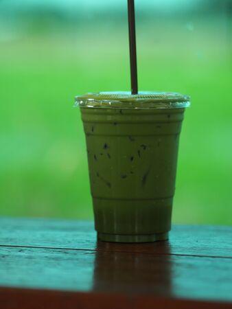 Matcha Green tea put milk ice in plastic glasses set on a wooden plate blurred of nature background 版權商用圖片