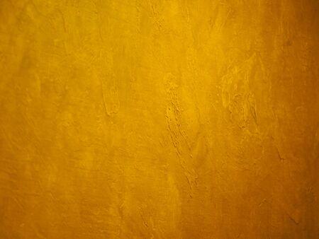 La superficie de la pared es rugosa, la pintura en fondo de material de textura dorada