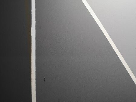 surface of the cement wall is rough, paint white line penetrates the middle between the dark gray and the light gray in texture material concrete background