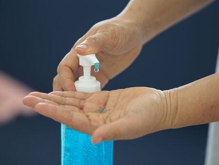 woman standing and pressing a pump bottle, Hand Sanitizer, gel alcoholic mixture with gelatin in clear Plastic bottle, washing clean dirty to prevent germs protect colona virus, covid 19