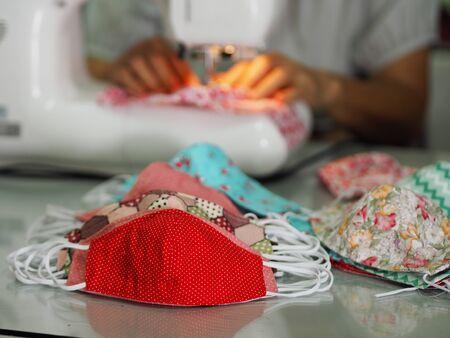 Une femme utilise une machine à coudre pour coudre un masque médical de protection contre la poussière PM 2.5, l'épidémie de coronavirus, le virus covid-19 Travail à domicile fait maison DIY