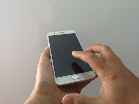 Woman hand is holding a mobile phone, Index finger is dabbing