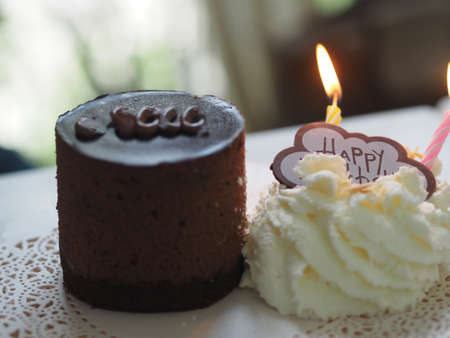 Dark Chocolate Birthday Cake piece on wooden plate candle with Whipped Cream on white paper