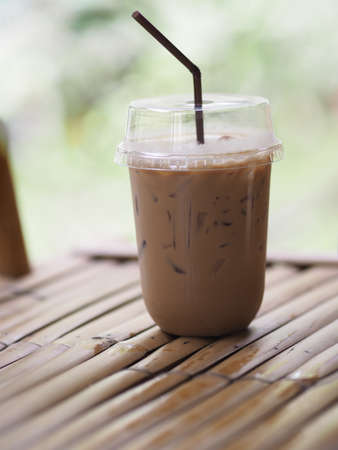 close up view of ice cubes in cold brewed coffee Cappuccino in plastic cup put on bamboo wooden desk blurred background, drink beverage