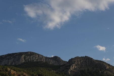 Great rocky mountain with pine trees an afternoon of clouds in the province of Granada 版權商用圖片