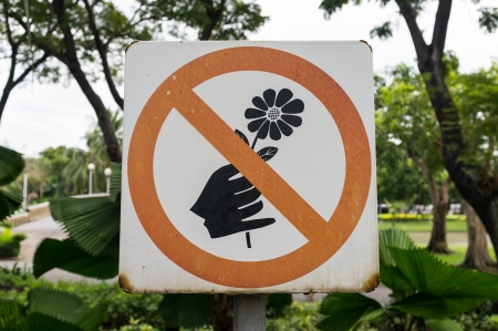 feeble: no picking flowers sign in public park Stock Photo