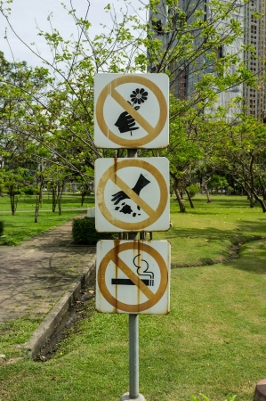 eco sensitive: 3 sign on park; no picking flowers, no trashing garbage and no smoking Stock Photo