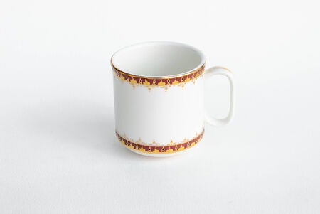 asian style crafted coffee cup with gold decoration isolated in white background