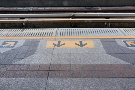 manage transportation: wait for the skytrain infront of way in and out sign Stock Photo