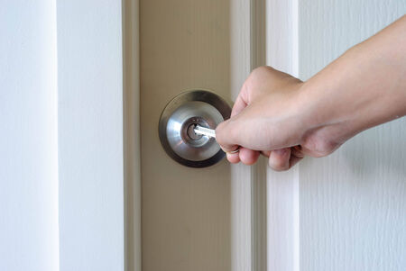 male hand try to unlocking round ball door knob by his key photo
