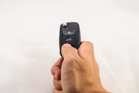 human hand pushing unlock button of car key isolated in white background photo