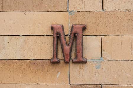men public restroom sign on brick wall photo