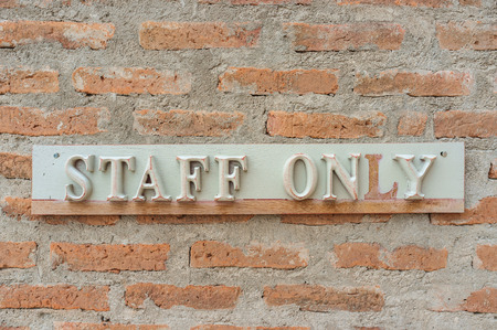 staff only: staff only sign with raw brick wall
