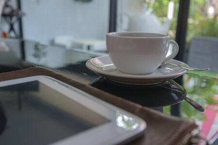 buena salud: que trabaja en caf� con la tableta inteligente y caf� Foto de archivo